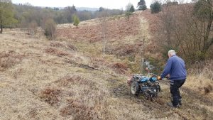 dog fence installer using his trencher on heavy terrain in the Ashdown Forest