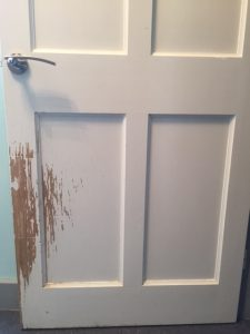 scratched door which can be prevented with indoor dog fence